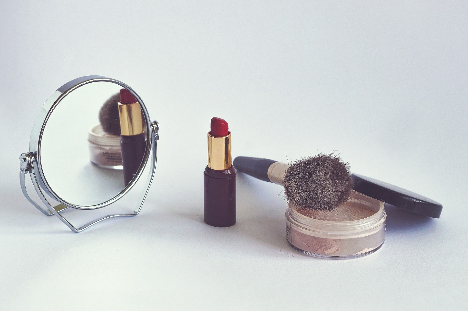 Na foto um batom vermelho, um iluminador, um pincel e um espelho.