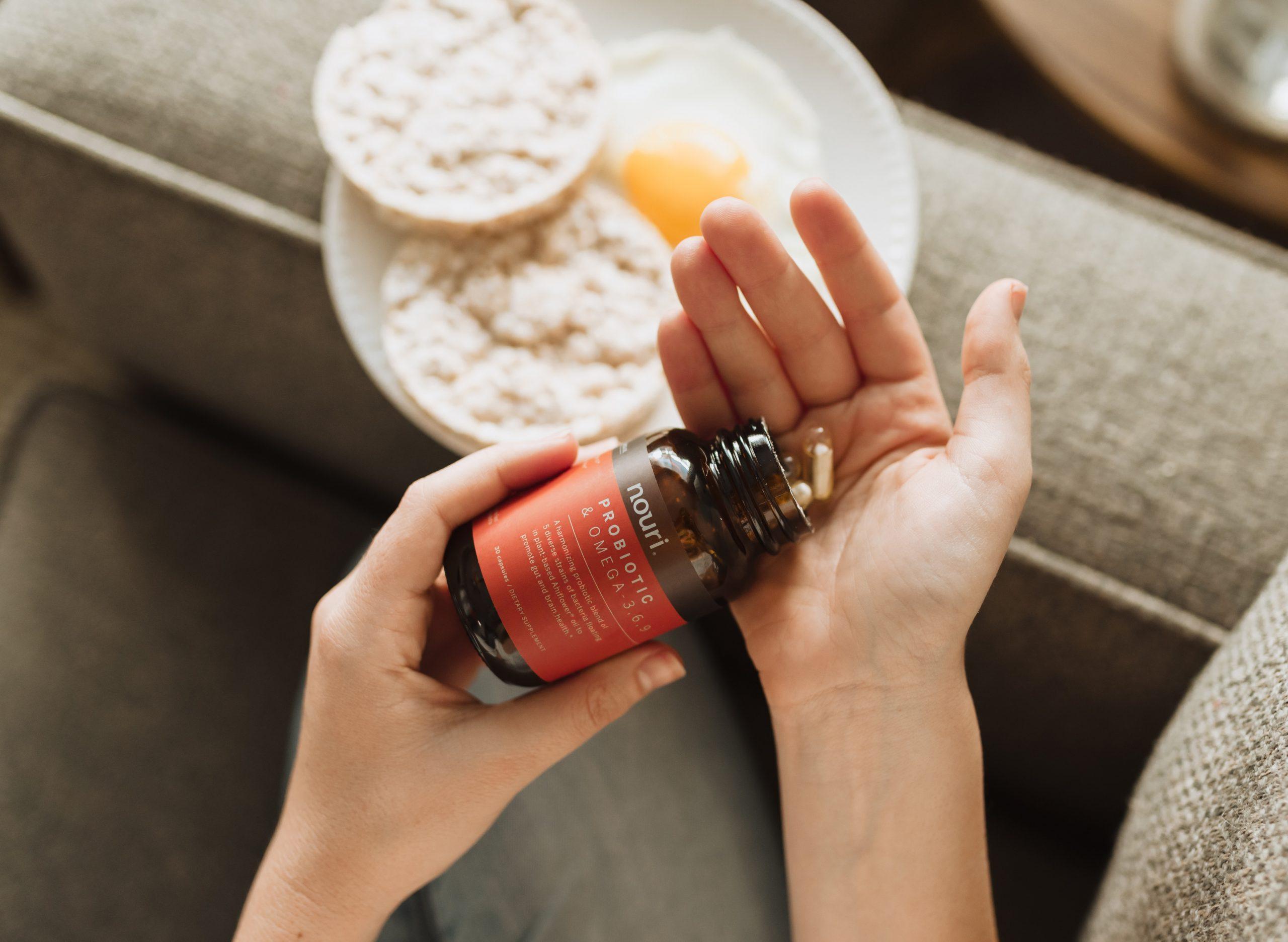 Imagem de uma pessoa colocando duas cápsulas na mão.