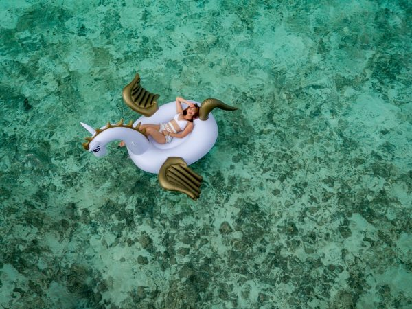 Na foto uma mulher em uma boia gigante no meio do mar.