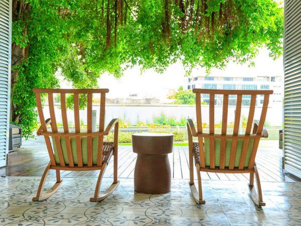 Duas cadeiras de madeira em uma varanda viradas para um jardim