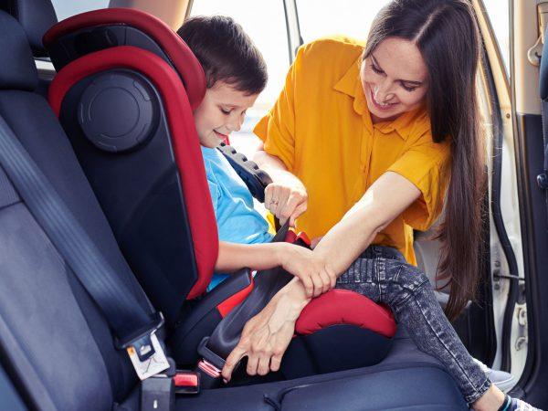 Mulher ajustando menino em uma cadeirinha de carro.