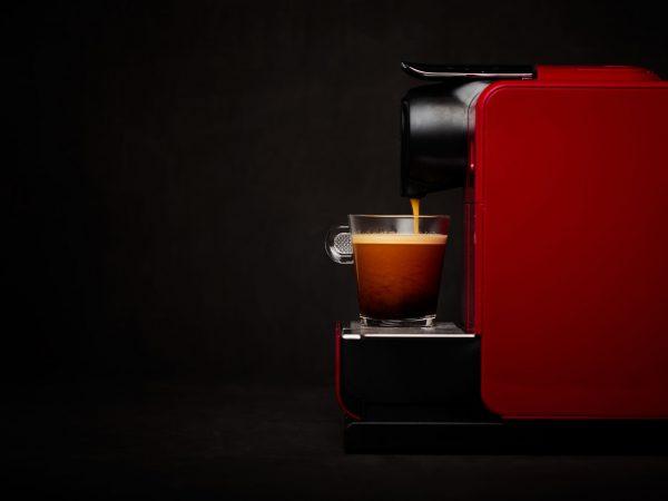 Na foto uma cafeteira vermelha de lado.