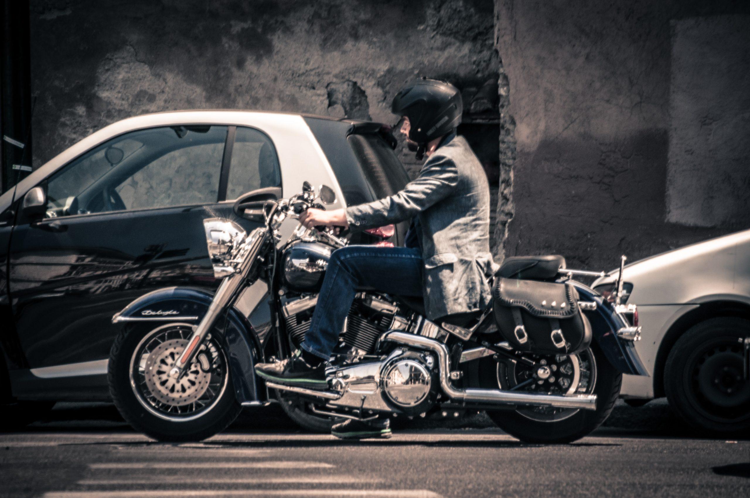 Imagem mostra um homem pilotando uma moto e usando um capacete.