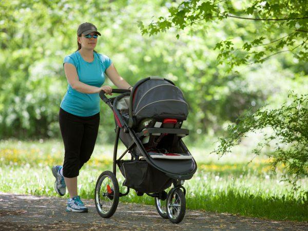 Mãe empurrando carrinho de bebê durante caminhada em parque.