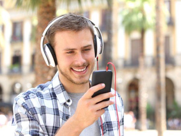 Homem andando e assistindo algo em seu celular com fone de ouvido