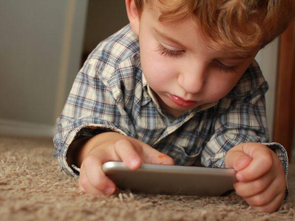 Imagem de um menino usando celular.