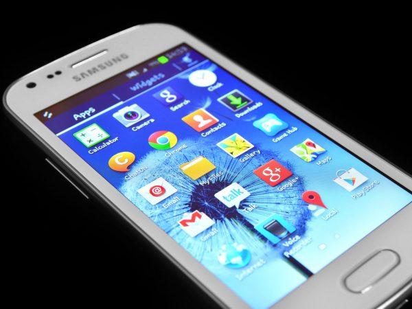 Celular Samsung branco com tela acesa