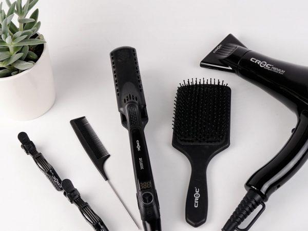 Na foto uma chapinha, uma escova de cabelo, um secador, um pente e outros acessórios.