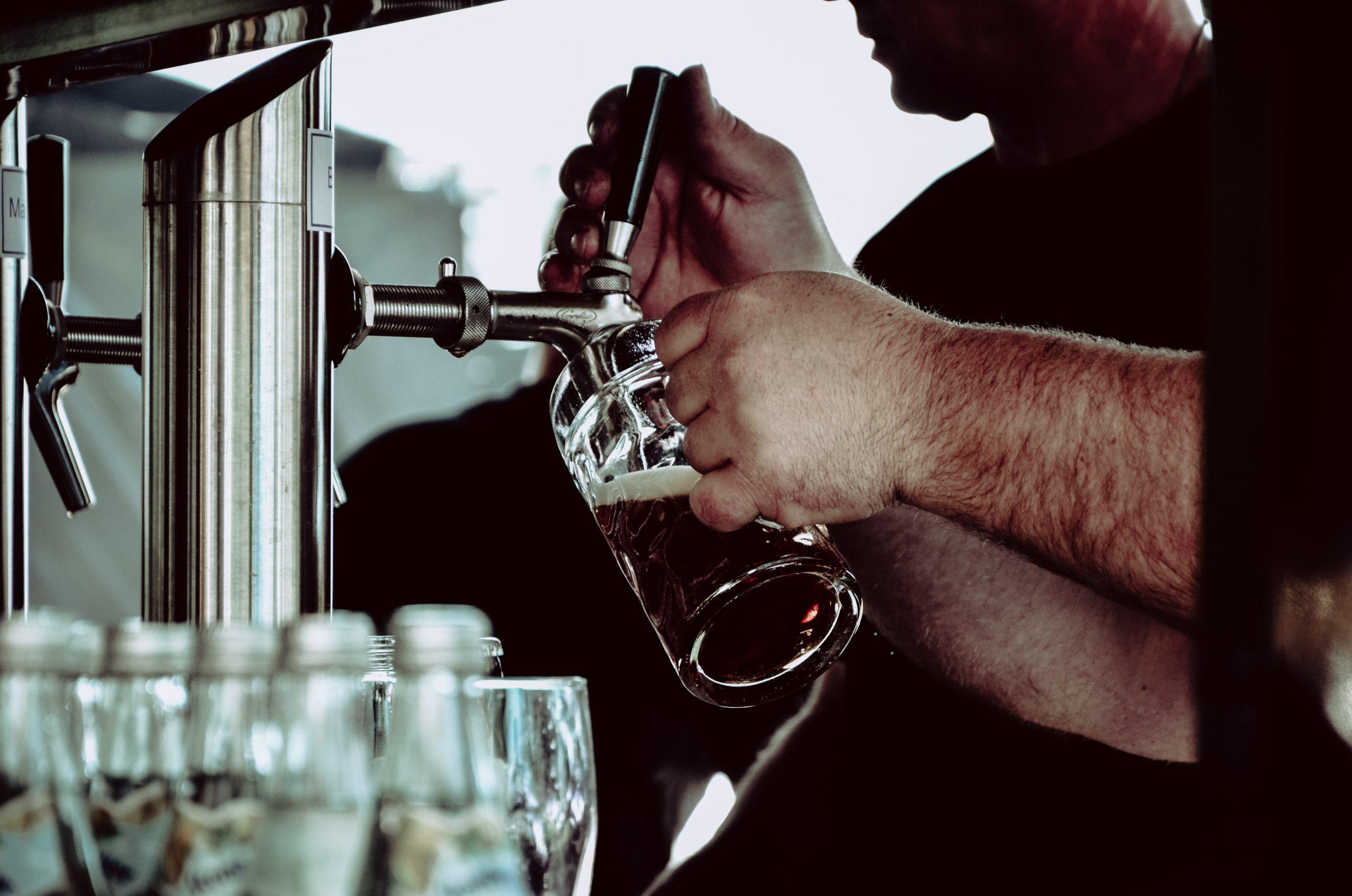 Imagem mostra uma chopeira elétrica em foco seletivo, enquanto um homem, representado apenas por seus braços, opera a torneira e serve um chopp numa caneca de vidro.