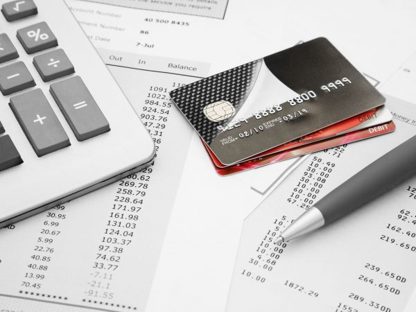 Calculadora, papeis com números, caneta e cartões.