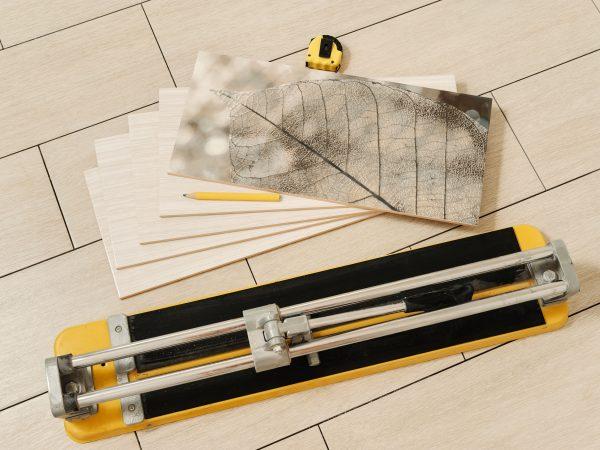 Imagem mostra um cortador de piso ao lado de vários pedaços de piso cortados.