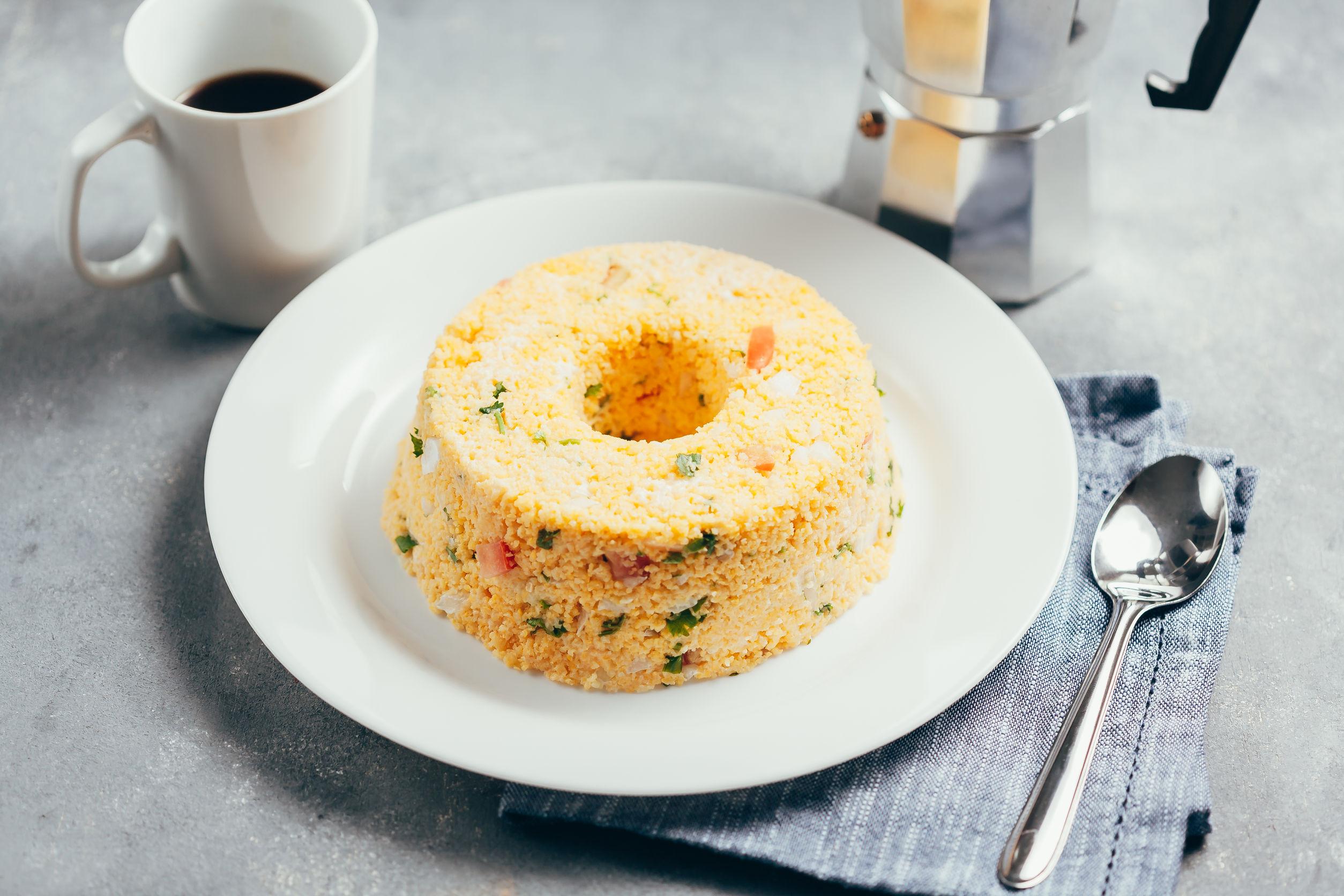 Cuscuz paulista servido em prato ao lado de adornos e bule de café