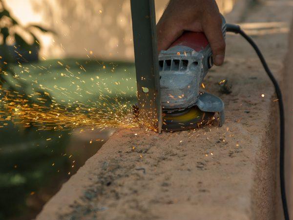 Imagem mostra uma esmerilhadeira sendo usada em um pedaço de metal.