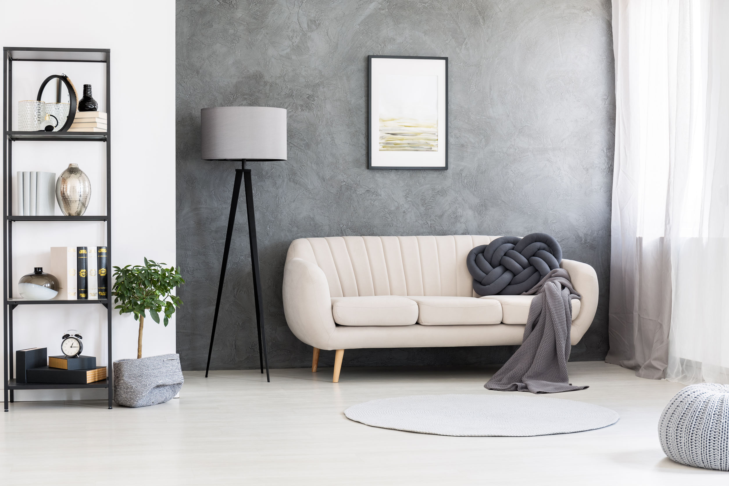Na foto uma sala de estar com estante, sofá, abajur e quadro na parede.