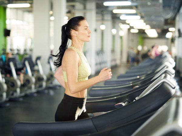 Imagem mostra uma mulher correndo numa esteira dentro de uma academia, com uma fileira de esteiras ao fundo.