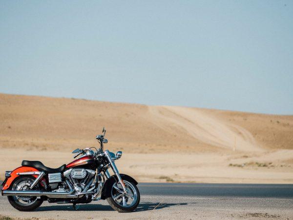 Moto na estrada com dunas ao fundo.