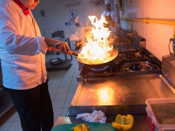 Imagem mostra um homem trabalhando com um fogão industrial.