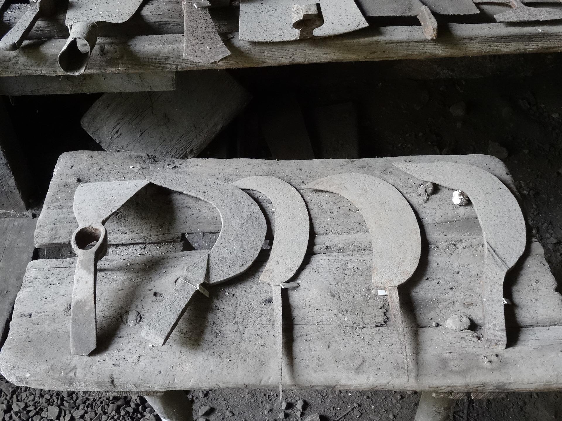 Imagem mostra várias foices empoeiradas lado a lado.