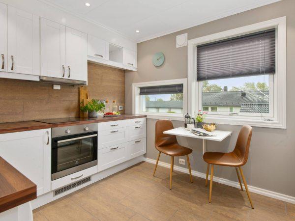 Na foto uma cozinha com armários brancos e uma mesa de dois lugares.