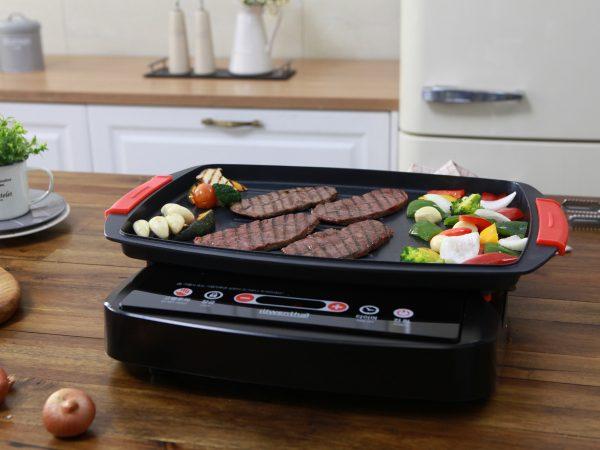 Na foto um grill com carnes e legumes em uma cozinha.