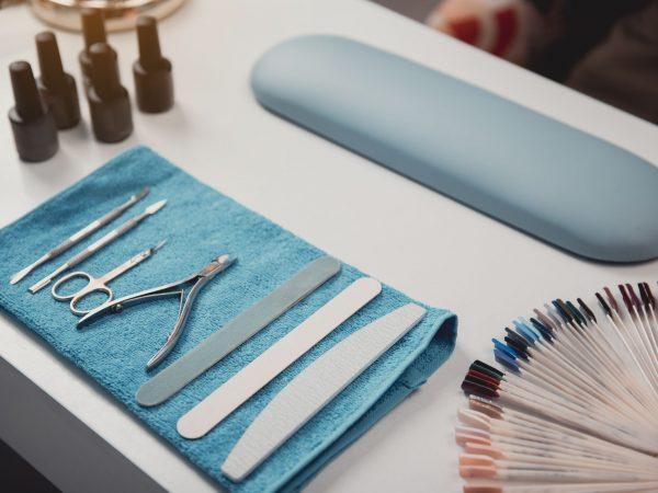 Na foto uma mesa com diversos produtos para as unhas como alicates, espátulas, lixas e amostras de esmalte.