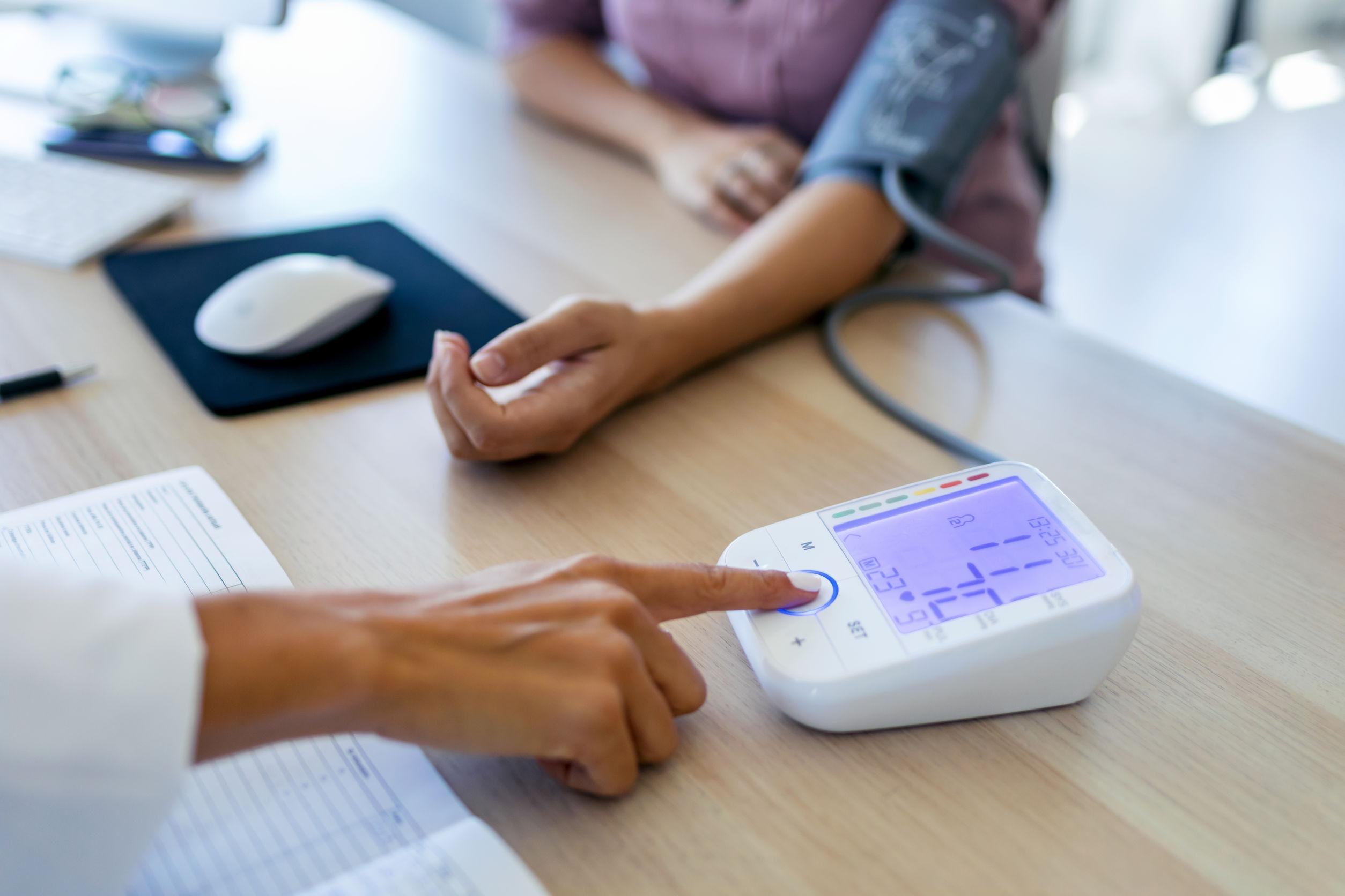 Na foto um médico aferindo a pressão de uma pessoa.