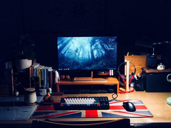 Imagem mostra uma escrivaninha iluminada por uma luminária de mesa, e repleta de itens, com um monitor ligado ao centro, mostrando a área de trabalho de um computador.