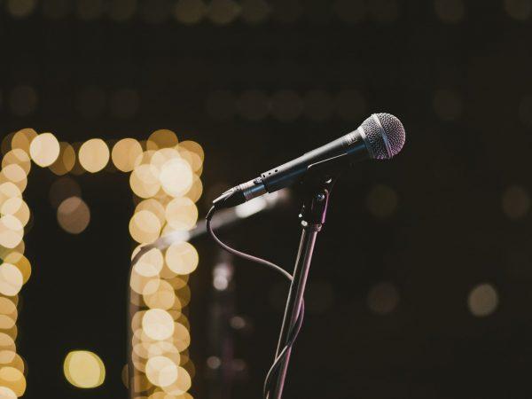 Imagem mostra, em foco seletivo, um microfone instalado num pedestal simples, com luzes desfocadas ao fundo.