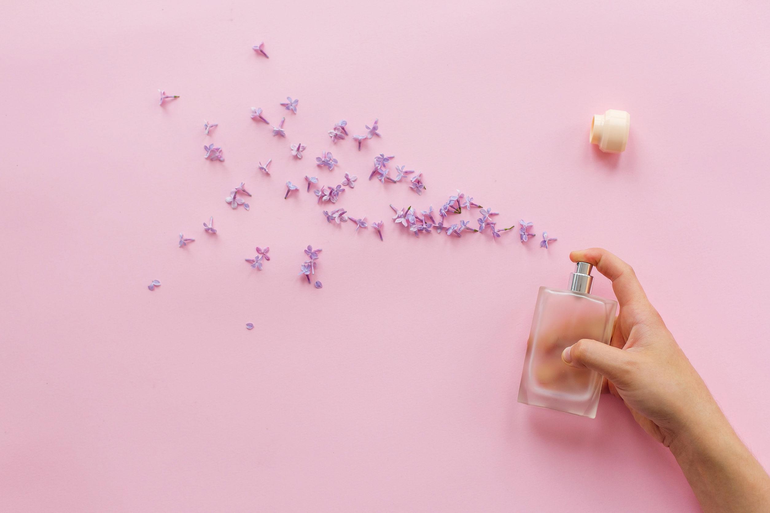 Mão apertando perfume e dele saem pétalas de flores
