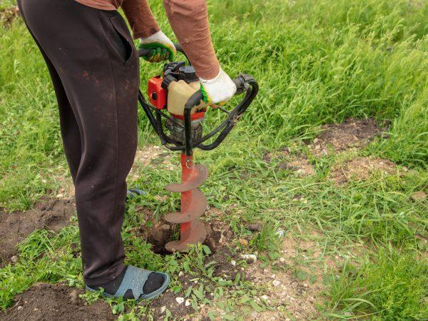 Imagem mostra uma pessoa usando uma perfuratriz para abrir um buraco no solo.