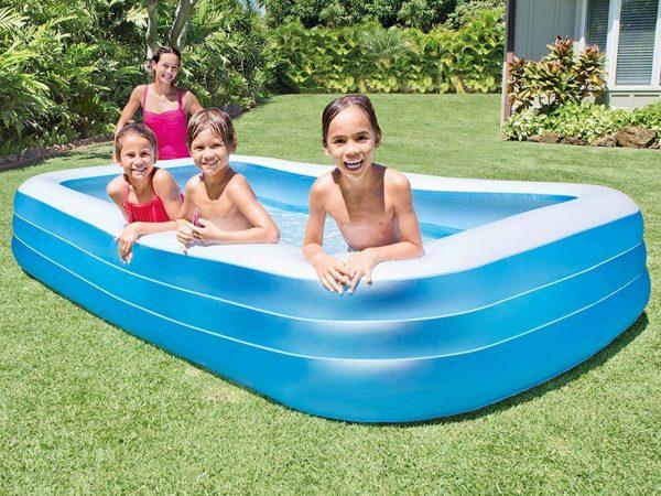 Piscina inflável com três crianças dentro sorrindo e olhando para a foto.