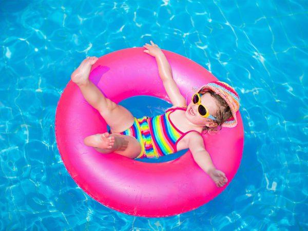 Menina deitada em boia rosa em uma piscina