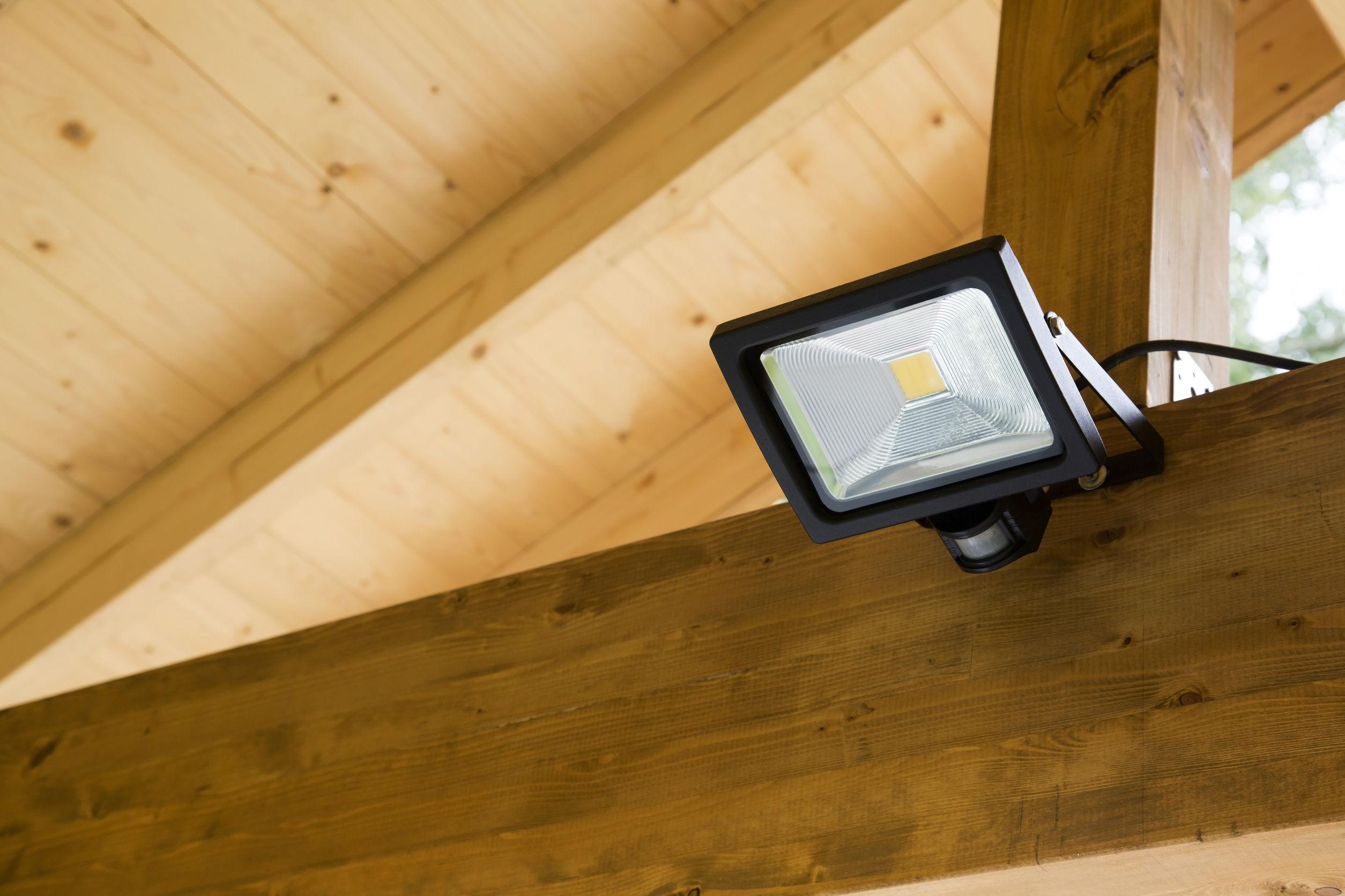 Imagem mostra um refletor LED instalado em uma estrutura de madeira.