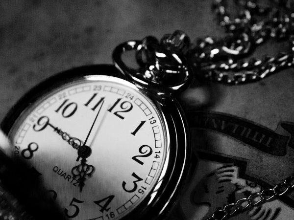 Na foto um relógio de bolso aberto com corrente na cor prata.