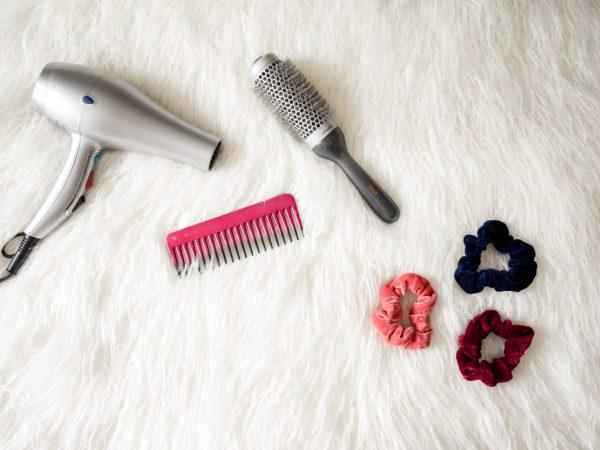 Na foto um secador de cabelo, uma escova, um pente e três elásticos.