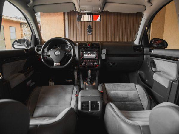 Imagem mostra o interior de um carro, sem pessoas, mas com um sistema de som instalado, e ligado, no painel.