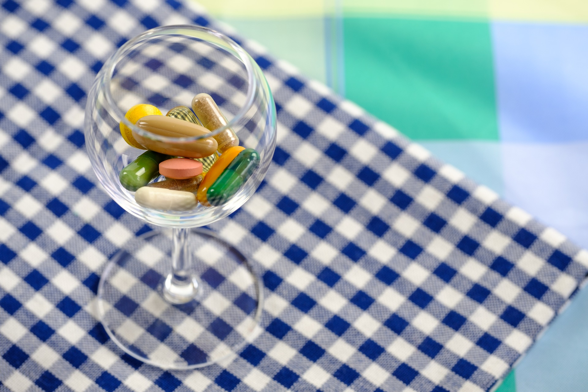 Taça com comprimidos dentro, sobre mesa com toalha de xadrez azul e branco.