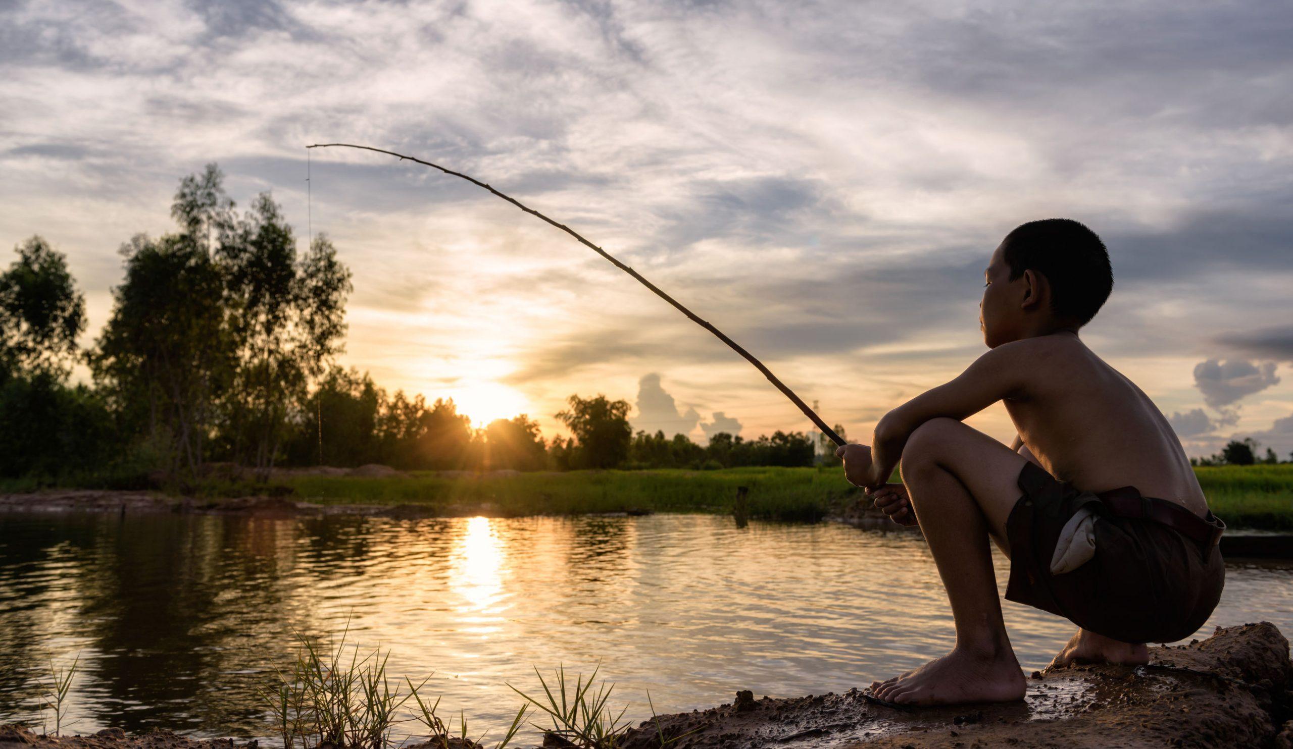 Imagem mostra um menino usando uma vara telescópica para pescar.