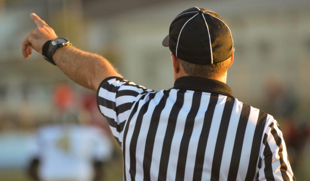 Imagem mostra um árbitro de futebol americano de costas, com a mão esquerda apontando para noroeste.