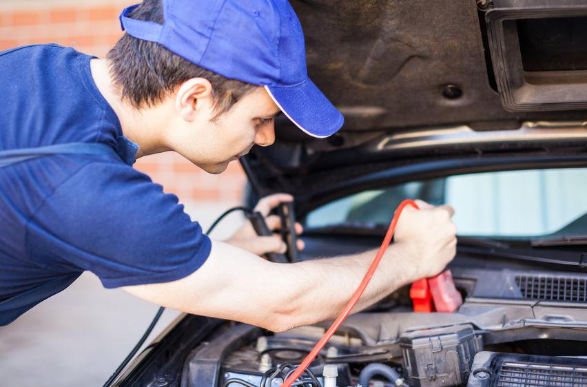 homem engatando fios na bateria do carro