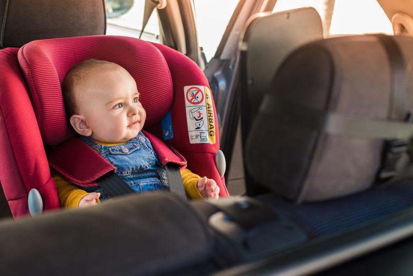 Bebê sentado em bebê conforto dentro do carro.