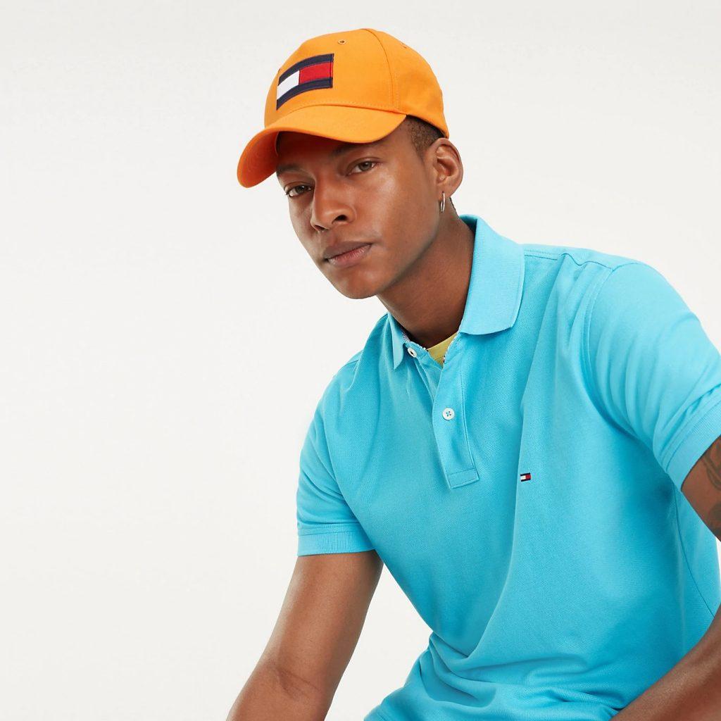 Um homem está sentado e olhando em direção à câmera, usando um boné Tommy alaranjado e usando uma camisa polo Tommy azul clara.