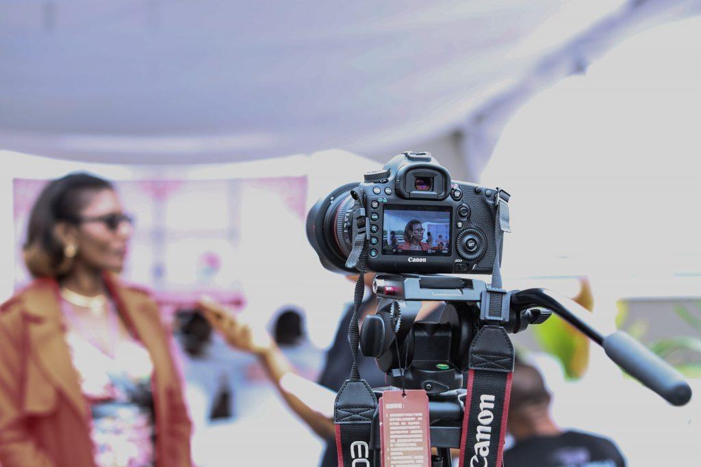 Câmera Canon em tripé com imagem de mulher na tela e em segundo plano.