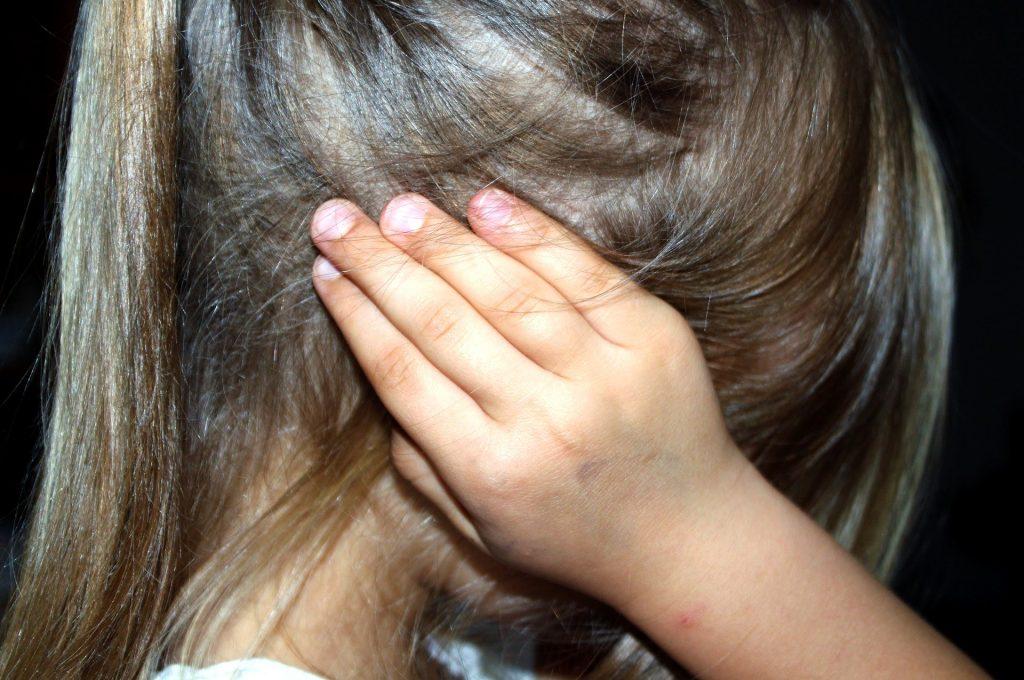 Uma criança com uma das mãos cobrindo a orelha.