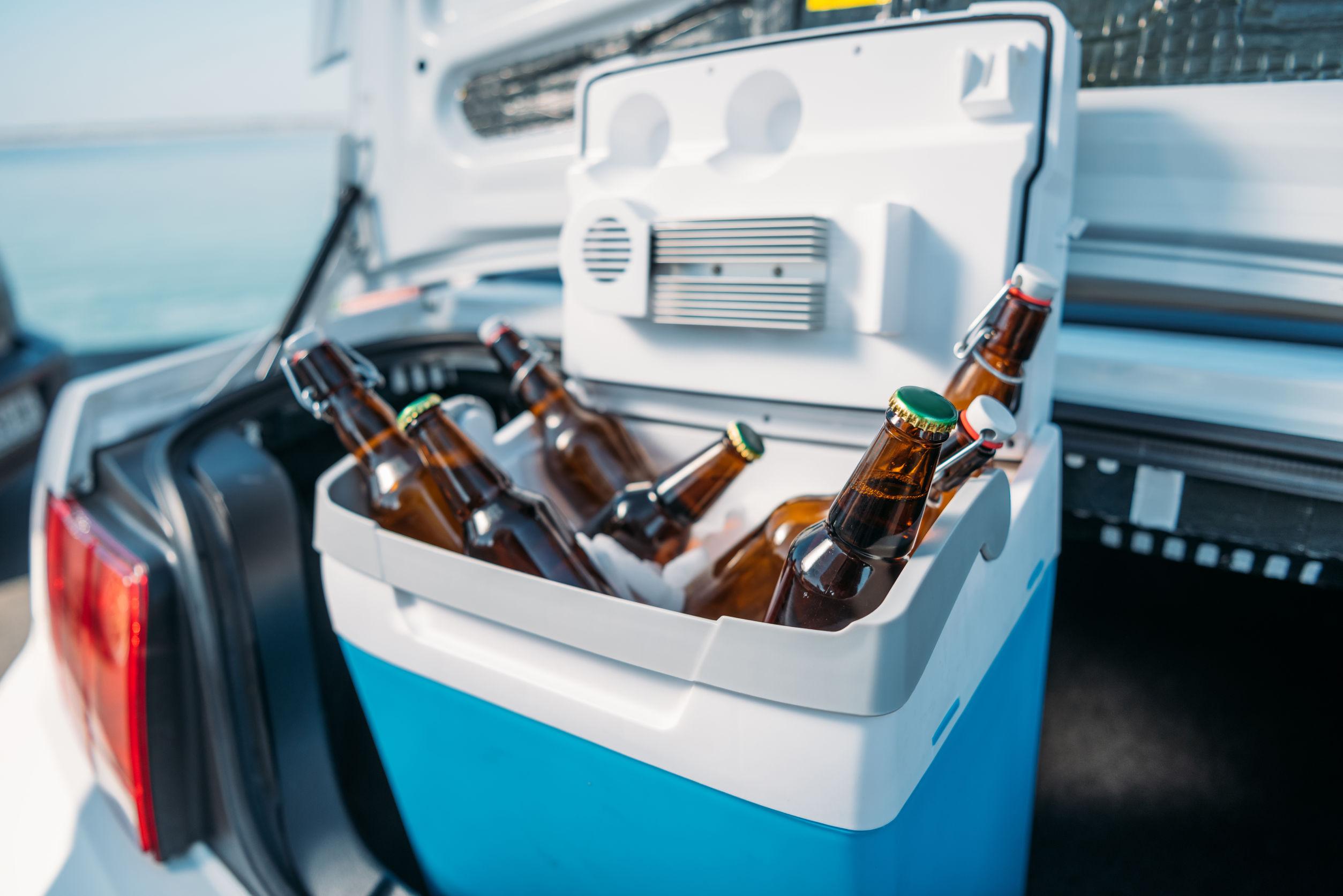 Imagem de um cooler azul aberto com cerveja dentro no porta malas do carro