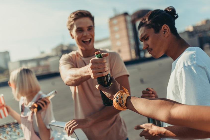 Amigos felizes pegando cerveja de um cooler