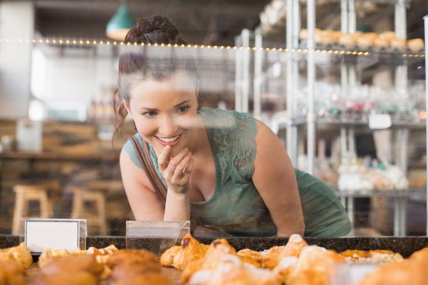 mulher indecisa vendo estufa para salgados em uma padaria