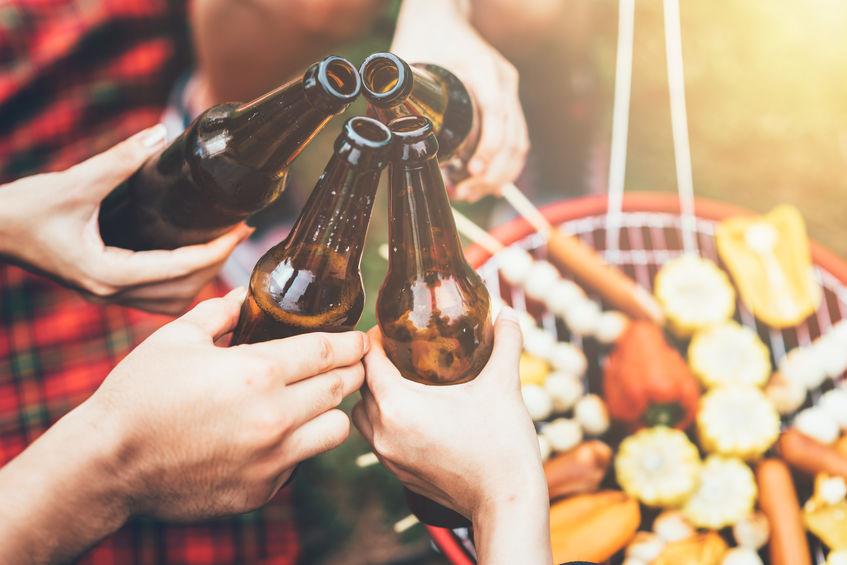 Imagem de quatro pessoas brindando com cerveja em um churrasco.