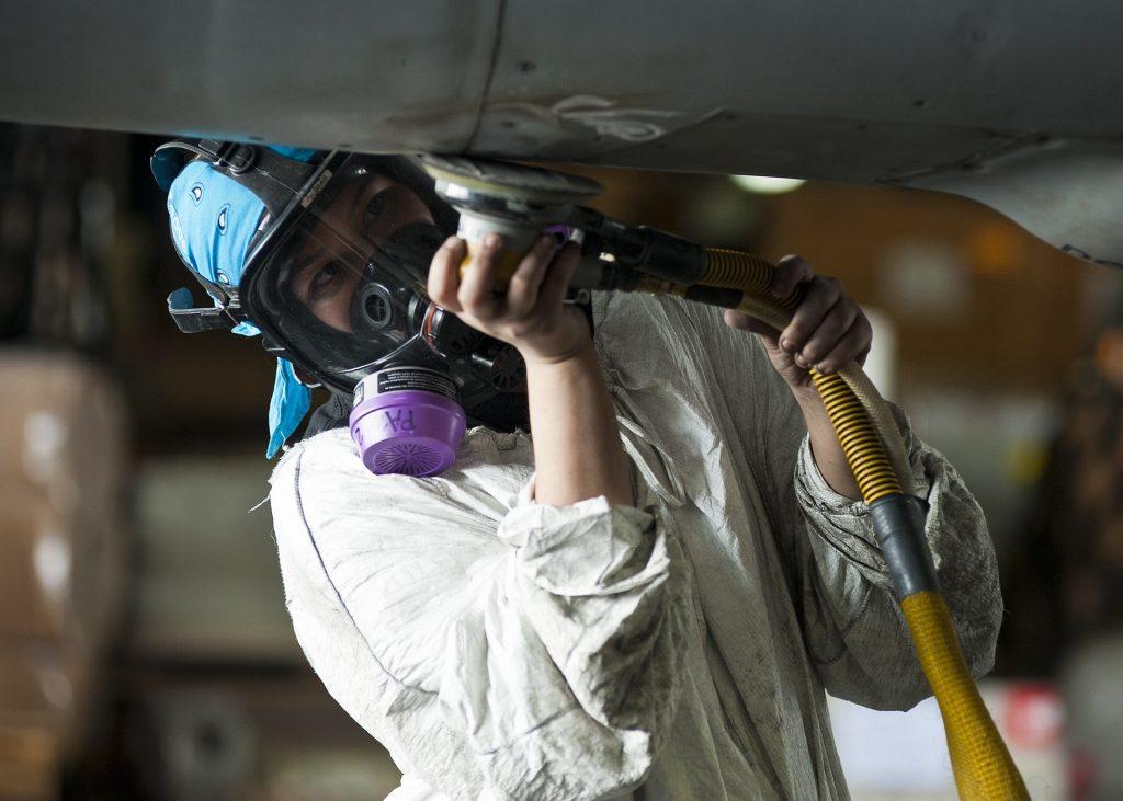 Uma pessoa realizando uma manutenção na parte externa de um avião