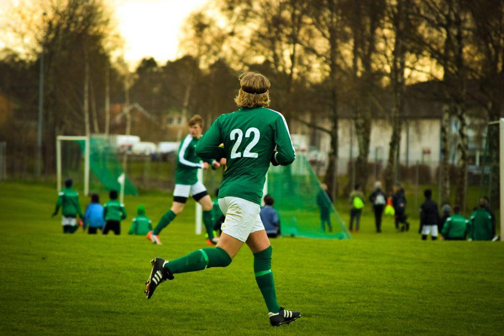 Imagem mostra ao centro um homem uniformizado correndo num campo de futebol. Seus meiões verdes são da mesma cor da camisa.